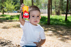Cute little child boy plays with toy car in park on nature at summer. Stock Images