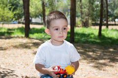 Cute little child boy plays with toy car in park on nature at summer. Royalty Free Stock Photos