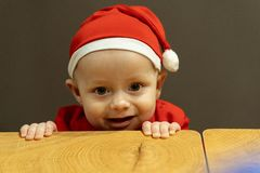 Cute little child boy in santa hat hold his hands at the table royalty free stock photography