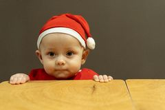 Cute little child boy in santa hat hold his hands at the table royalty free stock images