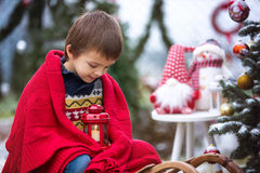 Cute little child, boy, sitting on a sledge next to a christmas Royalty Free Stock Photos
