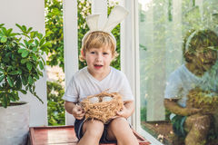 Cute little child boy wearing bunny ears on Easter day. Boy holding nest with eggs Stock Photography