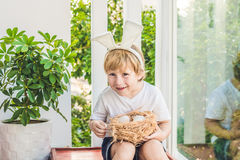 Cute little child boy wearing bunny ears on Easter day. Boy holding nest with eggs Royalty Free Stock Photos