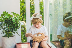 Cute little child boy wearing bunny ears on Easter day. Boy holding nest with eggs stock images