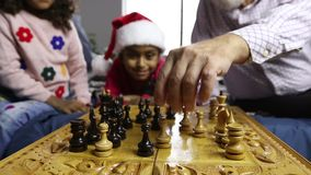 Cute girl capturing white pawn in chess game. Cute little child capturing white pawn while playing chess game with her grandfather on xmas. Happy mixed race girl stock video footage
