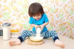 Cute little child cooks sitting on a table at home kitchen Stock Images