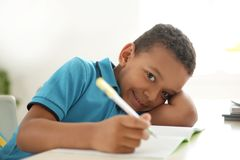 Cute little child doing assignment at desk Royalty Free Stock Image