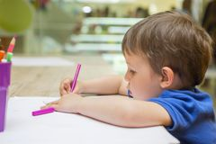 Cute little child is drawing with colorful felt-tip pens at home or kindergarten. Sitting at table in bright sunny playroom stock image
