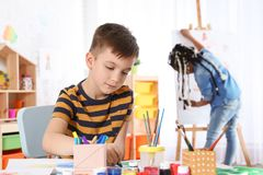 Cute little child drawing at painting lesson. Indoors stock image