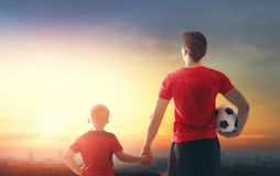 Boy with man playing football. Cute little child dreaming of becoming a soccer player. Boy with man playing football on sunset. Family sport Royalty Free Stock Images