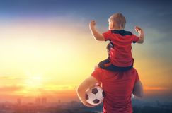 Boy with man playing football. Cute little child dreaming of becoming a soccer player. Boy with men playing football on sunset. Family sport Royalty Free Stock Photos
