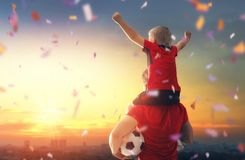 Boy with man playing football. Cute little child dreaming of becoming a soccer player. Boy with men playing football on sunset. Family sport Royalty Free Stock Image