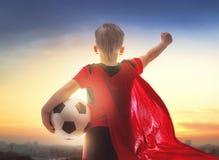 Boy playing football. Cute little child dreaming of becoming a soccer player. Boy playing football on sunset Stock Photo