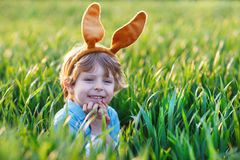 Cute little child with Easter bunny ears  in green grass Royalty Free Stock Images
