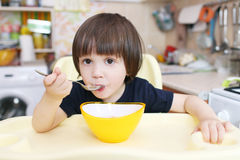 Cute little child eats soup at home Stock Image