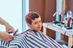 Cute little child is getting trendy haircut from barber at busy barbershop.  royalty free stock photos