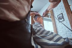 Cute little child is getting trendy haircut from barber at busy barbershop. Small school boy is getting trendy haircut from expirienced barber at modern stock image
