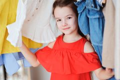 Cute little child girl choosing new modern clothes in her wardrobe or store fitting room. Kid fashion and apparel storage concept royalty free stock photo