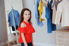 Cute little child girl choosing new modern clothes in her wardrobe or store fitting room. Kid fashion and apparel storage concept Royalty Free Stock Images