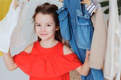 Cute little child girl choosing new modern clothes in her wardrobe or store fitting room. Kid fashion and apparel storage concept Royalty Free Stock Image