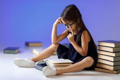 Cute little girl is reading a book. stock photo