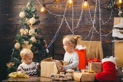 Cute little child girl is decorating the Christmas tree indoors. Christmas kids. Portrait of happy child looking at stock image