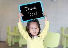 Cute little child girl holding blackboard showing text ` Thank You ` in kids room.