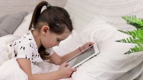 Cute little child girl lies in bed uses digital tablet. stock footage