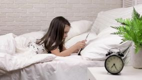 Cute little child girl lies in bed uses digital tablet. stock video