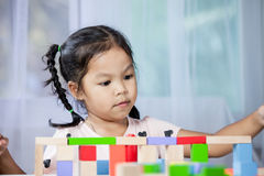Cute little child girl is playing with colorful wooden blocks Royalty Free Stock Images