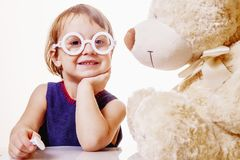 Cute little child girl playing dentist with teddy bear Children