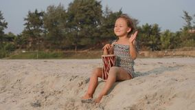 Cute little child girl playing drums on sandy beach. Happy kid having fun with ethnic drums outdoor stock footage