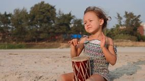 Cute little child girl playing drums on sandy beach. Cute little child girl playing drums on sandy beach in slow motion. Happy kid having fun with ethnic drums stock footage