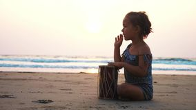 Cute little child girl playing drums on sandy beach. Cute little child girl playing drums on sandy beach in slow motion. Happy kid having fun with ethnic drums stock video
