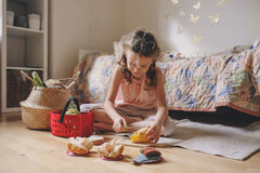 Cute little child girl playing in her room with toy food, cooking and having fun at home. Little child girl playing in her room with toy food, cooking and having Royalty Free Stock Photos