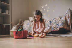 Cute little child girl playing in her room with toy food, cooking and having fun at home Stock Photos