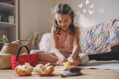 Cute little child girl playing in her room with toy food, cooking and having fun at home Royalty Free Stock Photo