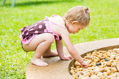 Cute little child girl in  playing with stones on a pebble beach Royalty Free Stock Photography