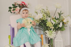 Cute little child girl with spring flowers, happy girl, kid in studio. Royalty Free Stock Image