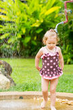 Cute little child girl in swimsuit bathing in shower on tropical resort Stock Photo