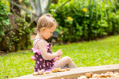 Cute little child girl in a swimsuit playing with stones on a pebble beach Royalty Free Stock Photos