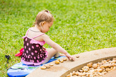 Cute little child girl in a swimsuit playing with stones on a pebble beach Stock Photography