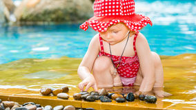 Cute little child girl in swimsuit playing with stones on pool in tropical resort Stock Photo