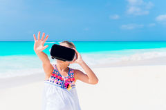 Cute little child girl using VR virtual reality goggles. Adorable girl look into the virtual glasses on white beach Royalty Free Stock Image
