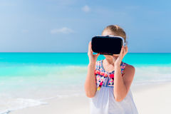 Cute little child girl using VR virtual reality goggles. Adorable girl look into the virtual glasses on white beach Stock Image
