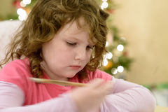 Cute little child girl writes the letter to Santa Claus near Christmas tree indoors. Royalty Free Stock Image