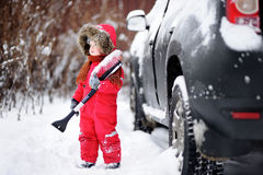 Cute little child helping to brush a snow from a car Royalty Free Stock Photography