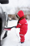 Cute little child helping to brush a snow from a car Stock Photo