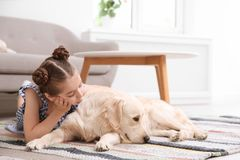 Cute little child with her pet on floor. At home stock photo