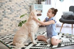 Cute little child with her pet on floor. At home royalty free stock photo